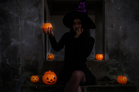 Young woman in witch Halloween costume hold a orange pumpkin with red eyes over scary dark background.