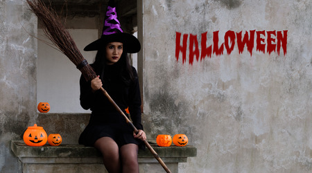 Young woman in witch Halloween costume is sitting and hold a witch's bloom with Halloween text on the wall over scary dark background.