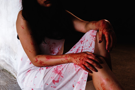 Horror Scene with woman cover the red blood on the body. Halloween concept. Stock Photo