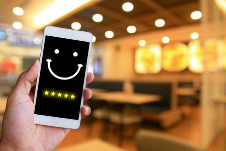 女性はスマートフォンで仮想タッチスクリーン上の顔顔文字を押しています。顧客サービス評価の概念。