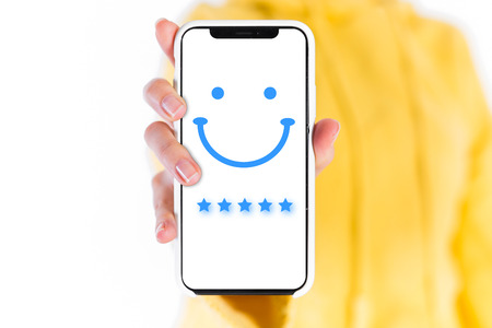 Woman is pressing face emoticon on virtual touch screen at smartphone. Customer service evaluation concept. Archivio Fotografico