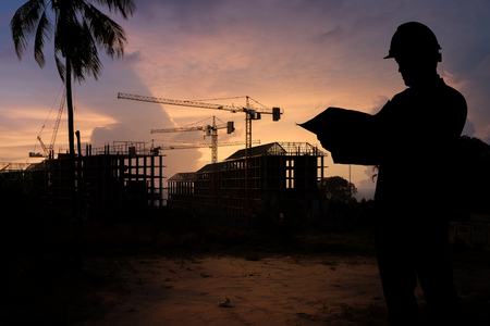 Silhouette engineer guy and construction site at Thailand in sunset time. Standard-Bild