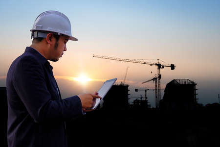 Engineer guy and silhouette construction site at Thailand in sunset time. Standard-Bild