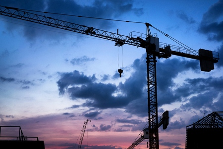 Silhouette tower crane and construction site at Thailand in sunset time. Standard-Bild