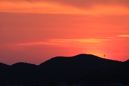 Golden time of sky at sunset - sunrise time in summer season. Dramatic sunset sky. The sunset time in Thailand. Sunset sky with silhouette of mountain.