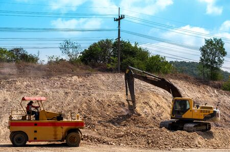 SATTAHIP, THAILAND %u2013 MARCH 22, 2019: Yellow excavator is working on extend highway at construction site.