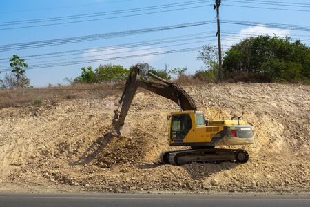 SATTAHIP, THAILAND %u2013 MARCH 22, 2019: Yellow excavator is working on extend high way at construction site.