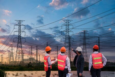 Silhouette high voltage electric tower and engineer team on sunset time and sky on sunset time background. Standard-Bild