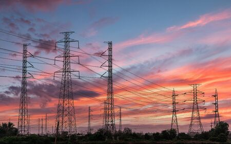 Silhouette high voltage electric tower on sunset time and sky on sunset time background. Banque d'images