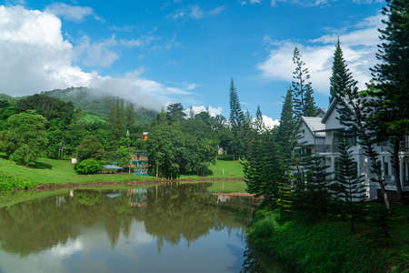 Clouds reflecting in the water. Surrounded by green vegetation. Rainny day with a blue sky and white clouds in Asia.