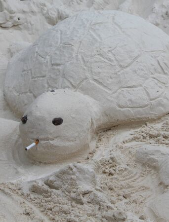 statue turtle from the white sand with a cigarette photo