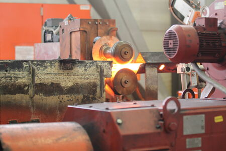 rollers: Moving the heated metal rod through the rollers in rolling mill Stock Photo