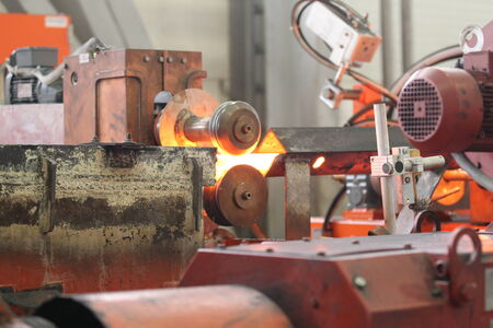 heated: Moving the heated metal rod through the rollers in rolling mill Stock Photo