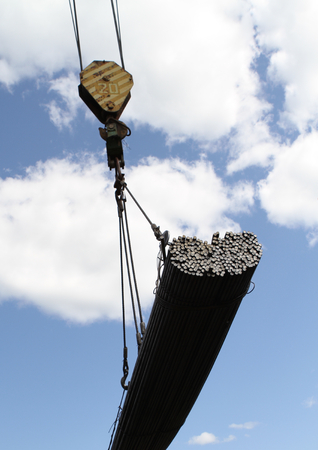 moves: crane lifts and moves a pack with metal reinforcement against the sky with clouds