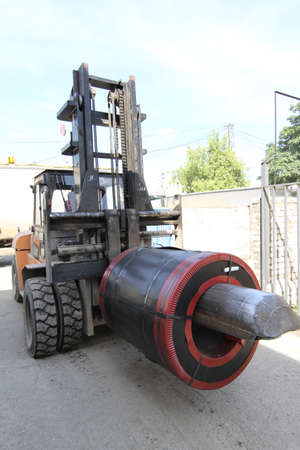 special steel: loader moves the roll of steel with the help of special equipment