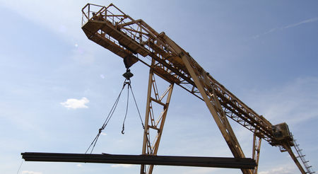 moves: gantry crane lifts and moves a pack with metal reinforcement against the sky with clouds