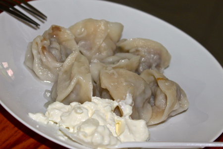 repast: Fresh ravioli with butter and sour cream on a white plate Stock Photo