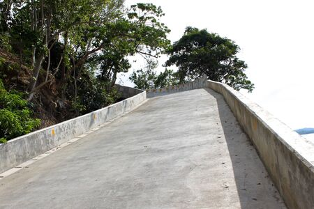 inclination: concrete road with large borders goes up Stock Photo