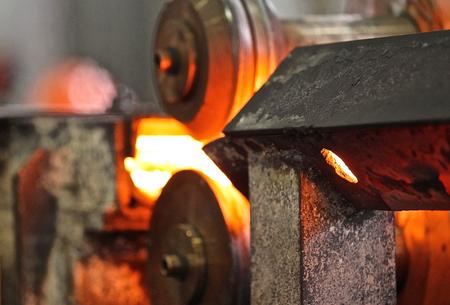 Le déplacement de la tige de métal chauffé à travers les rouleaux dans laminoir