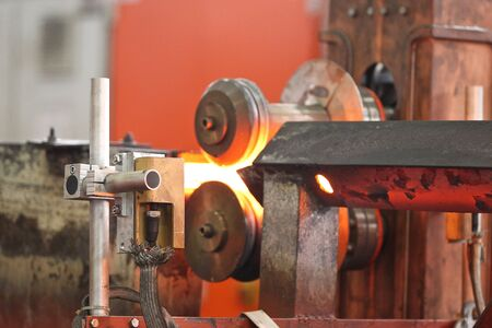 fabrication: Moving the heated metal rod through the rollers in rolling mill Stock Photo