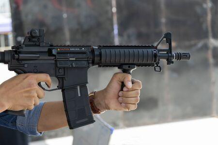 Un hombre con una pistola en la mano listo para disparar en defensa propia Foto de archivo