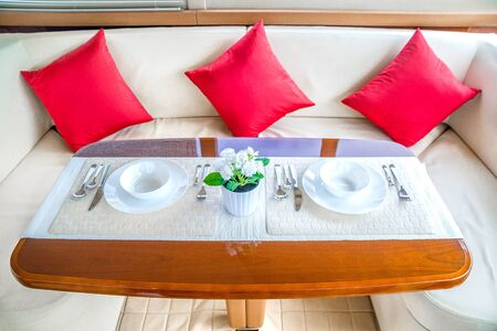 Luxury lunch table setting on a yacht interior comfortable design for holiday recreation tourism travel and vacation concept Stock Photo