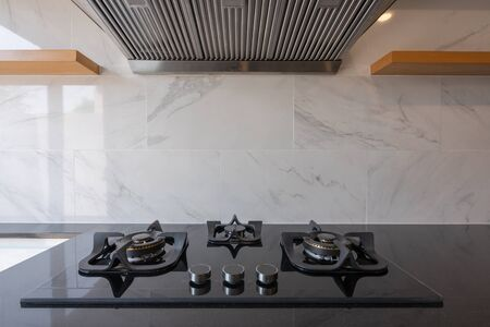 New kitchen gas stove on the black countertop and fume extractor interior furniture luxury home modern kitchen with white marble tiles wall interior contemporary