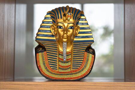 Antique Egyptian gold pharaoh Tutankhamen mask souvenir on wooden cabinet shelf for interior, Concept statues of King Pharaoh Egyptian gold mask culture symbol decoration