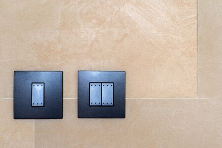 Set of black toggle lighting switches installed on a brown ceramic wall decoration modern building architecture with space for text and advertising
