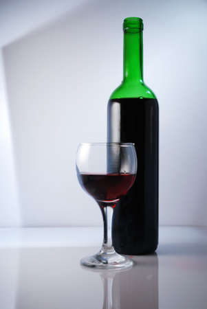 nonuniform: Glass and bottle of red wine on a non-uniform background Stock Photo
