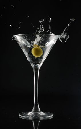 Martini with an olive on a black background