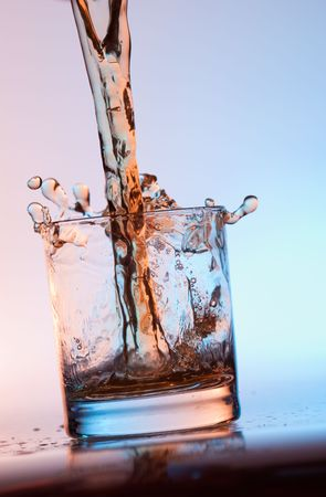 The stream filling an empty glass by alcohol