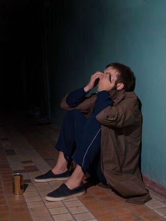 Homeless man sitting on floor photo