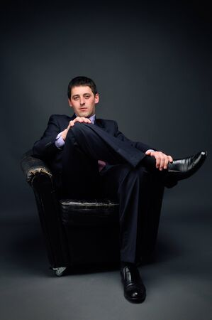Young bussinessman sitting in black chair Stock Photo