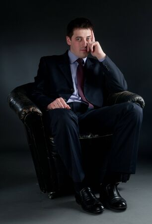 bussinessman: Young bussinessman sitting in black chair Stock Photo