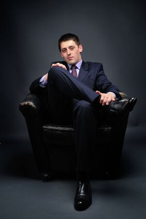 lawer: Young bussinessman sitting in black chair Stock Photo