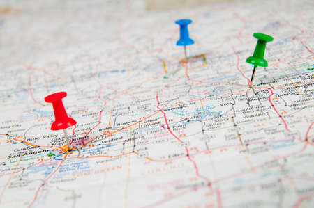 map pins: Color pushpins marking a location on a road map.