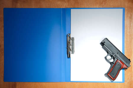 Concept with pistol and blank paper photo