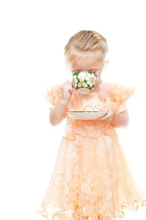 Little girl with cup of tea isolated on white photo