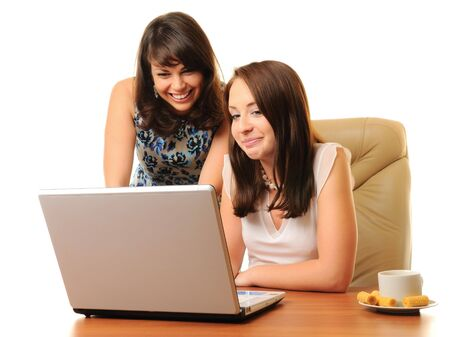 Two young businesswoman with laptop isolated over white Stock Photo - 7864371