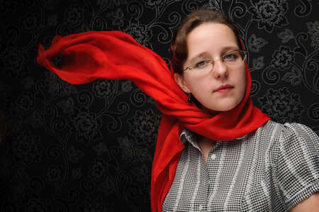 Charming woman over dark background with red shawl on the wind photo