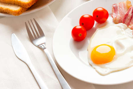 English breakfast with egg, bakon and tomatoes photo