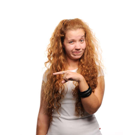 wrinkled brow: Cute ginger girl pointing at something with wrinkled face