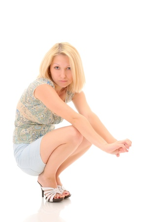 Pretty blonde squatting over white backround photo