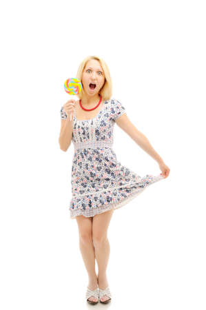 Attractive surprised  blonde with lollipop holding her dress, looking like a littile girl Stock Photo - 8616441
