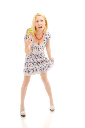 Attractive surprised  blonde with lollipop holding her dress, looking like a littile girl Stock Photo