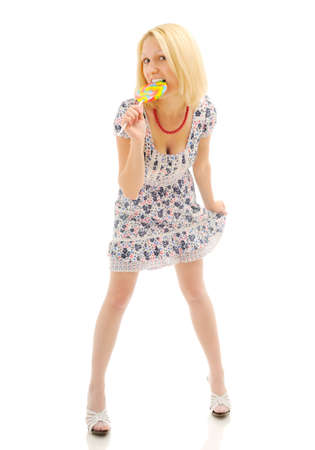 Attractive blonde eating lollipop and holding her dress Stock Photo