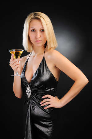 Sexy blonde standing with goblet, hand on hip photo