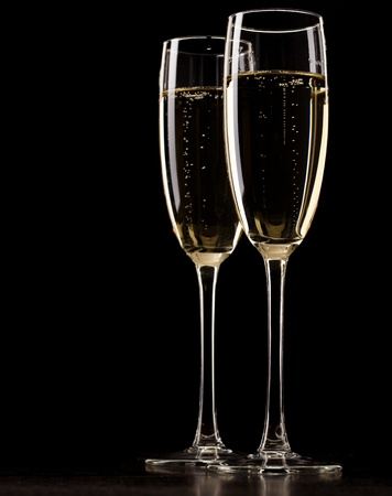 Two full glasses of champagne over dark background photo