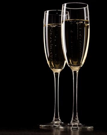 champagne glasses: Two full glasses of champagne over dark background
